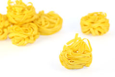 Italian pasta - tagliatelli. Nests of italian pasta, isolated on white background. The image is taken with a high-quality macro Royalty Free Stock Photography