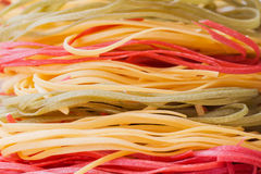 Italian pasta, three color from durum wheat with vegetables on the kitchen textiles, background, selective focus. for Royalty Free Stock Photography