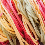 Italian pasta, three color from durum wheat with vegetables on the kitchen textiles, background. Top view. Macro. for Royalty Free Stock Image