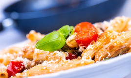 Italian pasta with tomato sauce and cheese as decoration green basil leaves. Macro Royalty Free Stock Photo