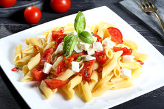 Italian pasta with tomatoes and mozzarella cheese Stock Image