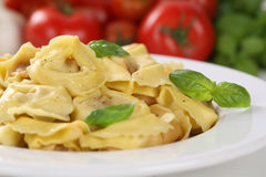 Italian Pasta Tortellini noodles meal with tomatoes and basil on Royalty Free Stock Image