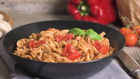 Italian pasta with tuna and basil. Fresh pasta with tuna and tomato sauce on old wooden background stock footage