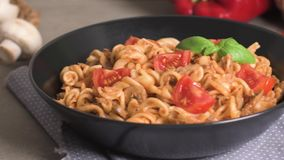 Italian Pasta with Tuna and Basil. Fresh pasta with tuna and tomato sauce on old wooden background stock video footage