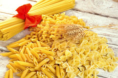Italian pasta uncooked. On wooden board Royalty Free Stock Photography