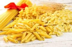 Italian pasta uncooked. On wooden board Stock Photo