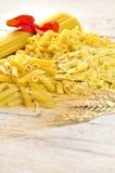Italian pasta uncooked. On wooden board Stock Photos
