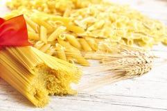 Italian pasta uncooked. On wooden board Royalty Free Stock Photos