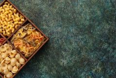 Italian pasta. Various types and shapes of Italian pasta on dark background, top view, with place for text Stock Photos