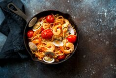 Italian Pasta With Tomato Sauce, Scallops And Shrimps In A Skillet Stock Images