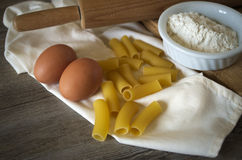 Italian pastasciutta. Rigatoni with eggs and flour. Italian pasta, rigatoni on wooden table in low light with eggs and flour Royalty Free Stock Images