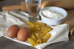 Italian pastasciutta. Rigatoni with eggs and flour. Italian pasta, rigatoni on wooden table in low light with eggs and flour Stock Photos