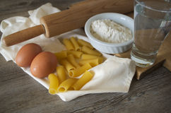 Italian pastasciutta. Rigatoni with eggs and flour. Italian pasta, rigatoni on wooden table in low light with eggs and flour Stock Images