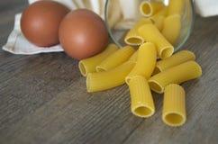 Italian pastasciutta. Rigatoni with eggs. Italian pasta, rigatoni on wooden table in low natural morning light Royalty Free Stock Images