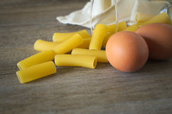 Italian pastasciutta. Rigatoni with eggs. Italian pasta, rigatoni on wooden table in low natural morning light Stock Photo