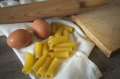 Italian pastasciutta. Rigatoni with eggs. Italian pasta, rigatoni on wooden table in low natural morning light Royalty Free Stock Images