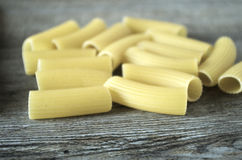 Italian pastasciutta. Rigatoni. Italian pasta, rigatoni on wooden table in low natural morning light Stock Photography