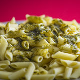 Italian penne pasta  green pesto sauce on a red background. Royalty Free Stock Photography