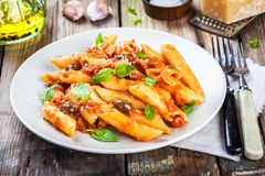 Italian penne pasta. With tomato sauce, olives and basil Stock Photos