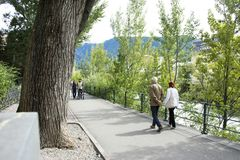 Italian people and foreigner travelers walking relax on footpath at riverside of passer river in Merano, Italy. Italian people and foreigner travelers walking stock photo