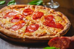 Italian Pepperoni pizza with mozzarella cheese and salami on wooden board. Close up royalty free stock photo