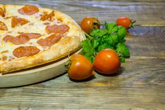 Italian Pepperoni pizza with salami on dark wooden background. Italian traditional food. A textured background. Copy paste place Royalty Free Stock Images