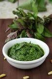 Italian pesto sauce. On a wooden board with basil stock photo