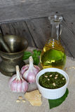 Italian pesto sauce and ingredients. On a dark wooden background Royalty Free Stock Photo