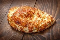 Italian pirogue pizza on wooden table with melting baked cheese. Delicious italian fast food. Calzone pizza royalty free stock photos