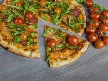 Italian pizza al forno. Traditional Italian pizza al forgo with rocket and cherry  tomatoes Stock Image