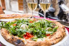 Italian pizza with arugula. Tomato and cheese on the table in a restaurant outside over blurred background stock photo