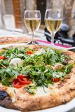 Italian pizza with arugula. Tomato and cheese on the table in a restaurant outside over blurred background stock images