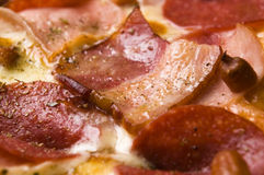 Italian pizza with bacon, salami and cheese Stock Image