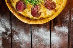 Italian pizza with beef on a wooden table royalty free stock photo