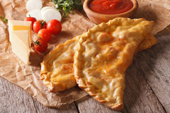 Italian pizza calzone closeup on a paper and ingredients. horizo Royalty Free Stock Photography