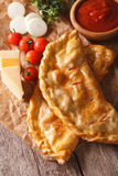 Italian pizza calzone closeup on a paper and ingredients. Vertic Stock Photos