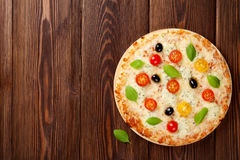 Italian pizza with cheese, tomatoes, olives and basil stock photography