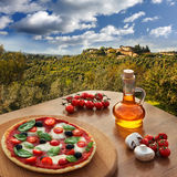 Italian pizza in Chianti against olive trees and villa in Tuscany, Italy. Italian pizza in Chianti with olive trees and villa in Tuscany, Italy Royalty Free Stock Images