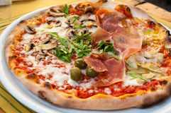 Italian pizza. Close-up of an italian pizza with prosciutto ham, green olives and rucola royalty free stock photo