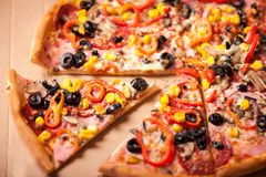 Italian Pizza closeup with a cut slice. Pizza with ham, pepperon Royalty Free Stock Photography