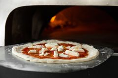 Italian pizza is cooked in a wood-fired oven. Close up stock photography