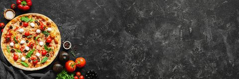 Italian pizza and pizza cooking ingredients on black concrete background. Tomatoes on vine, mozzarella, black olives, herbs and spices. Copy space for text royalty free stock photos
