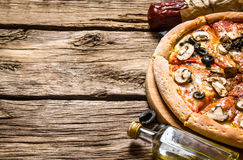 Italian pizza and different ingredients - meat, mushrooms, tomatoes and olive oil. Royalty Free Stock Image