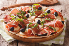 Italian pizza with figs, prosciutto, herbs, olives and mozzarell. A closeup on the table. horizontal stock photography