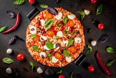 Italian pizza with ingredients. Italian pizza on grill board with various ingredients on dark background top view copy space stock image