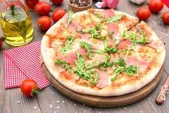 Italian pizza with ham and arugula. Italian pizza with ham arugula and cheese Royalty Free Stock Photography