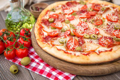Italian pizza with ham and olives. Italian pizza with ham olives and cherry on a wooden board Stock Photo