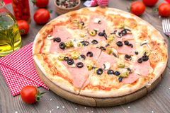Italian pizza with ham and olives. Italian pizza with ham olives and mushrooms Royalty Free Stock Images