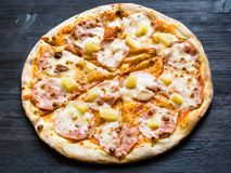 Pizza with ham and pineapple on dark wooden board stock image