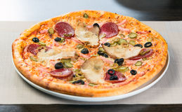 Italian pizza. With ham tomato and olives Stock Photos